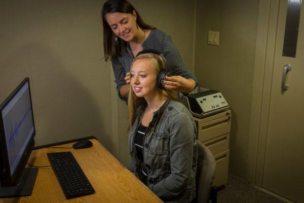 lab member putting headphones on listener